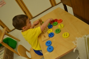 A young 3-year-old learns to sort by number of holes on circle.