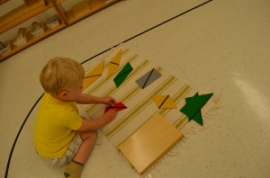 In Sensorial Area, a young child learns differing quad. shapes through Rectangle Box  I
