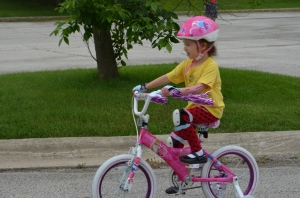 This child uses all of her coordination and concentration to master riding her bicycle.